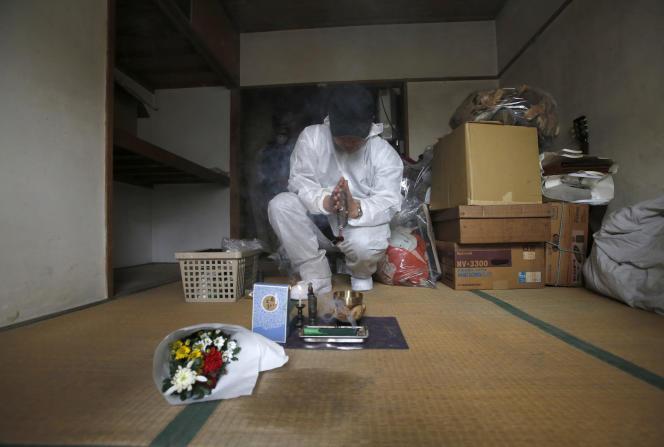 Un employé spécialisé dans les « morts solitaires » prie à l'endroit où un homme de 85 ans a été retrouvé mort, à Tokyo, en mars 2015.