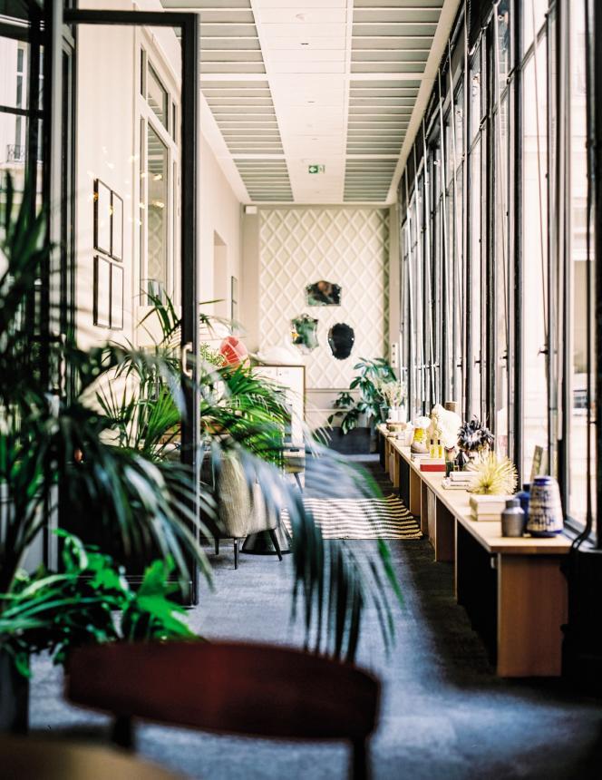 Une pièce aménagée comme un jardin d'hiver surplombe une cour intérieure.