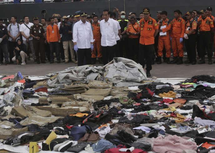 Le président indonésien,Joko Widodo (au centre), et le ministre des transports,Budi Karya Sumadi (à gauche), devant les débris de l'appareil et les effets personnels des victimes, mardi 30 octobre, à Djakarta.