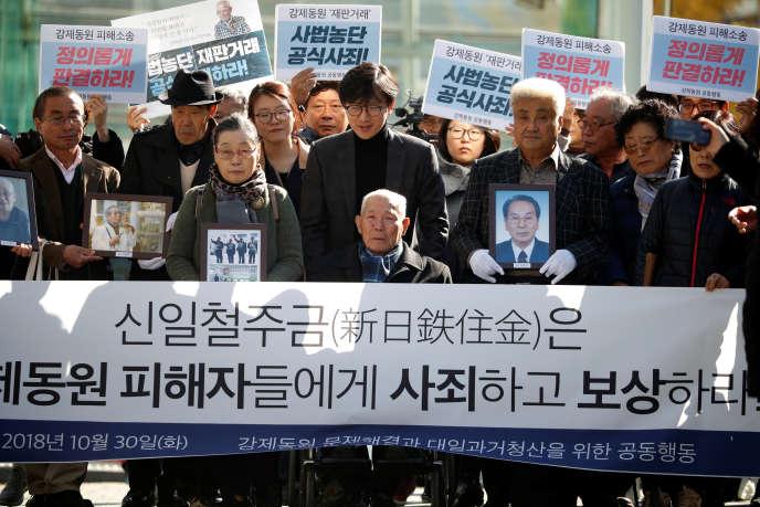 Lee Choon-shik (au centre), une victime de travail forcé au Japon pendant la seconde guerre mondiale, entouré de ses soutiens, le 30 octobre à Séoul. Sur la banderole : «Nippon Steel & Sumitomo Metal,excusez-vous auprès des travailleurs forcés et indemnisez-les».