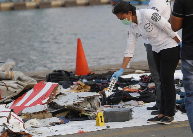 Un officier de police inspecte les débris du crash de l'appareil de Lion Air à Jakarta le 29 octobre 2018.