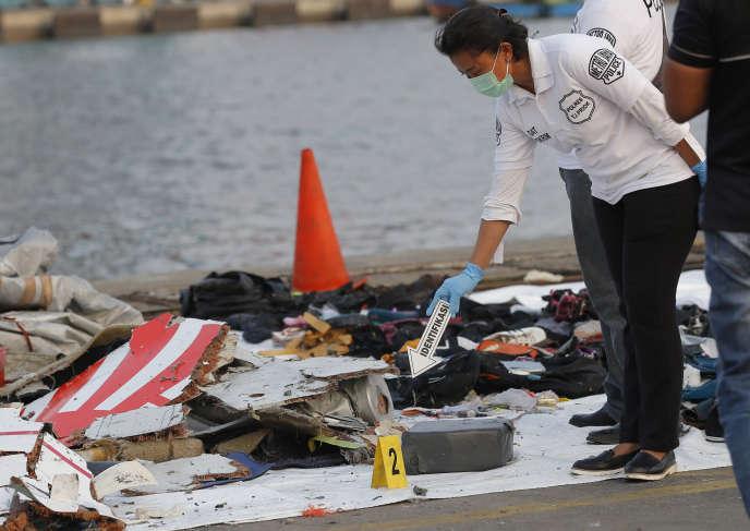 Un policier inspecte des débris de l'appareil Lion Air qui s'est abîmé en mer, au port de Tanjung Priok, à Jakarta, lundi 29 octobre.