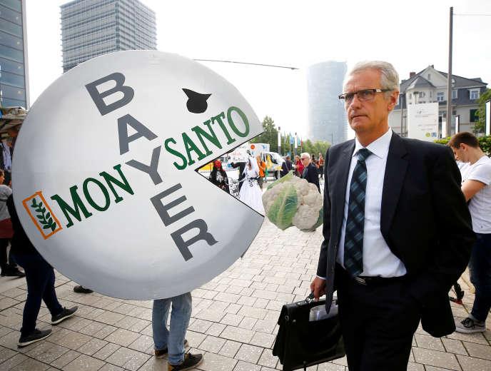Un actionnaire de Bayer devant un manifestant contre la fusion entre Monsanto et Bayer, à Bonn (Allemagne), le 25 mai.