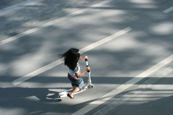 Paris, fillette faisant de la trottinette sur une piste cyclable.