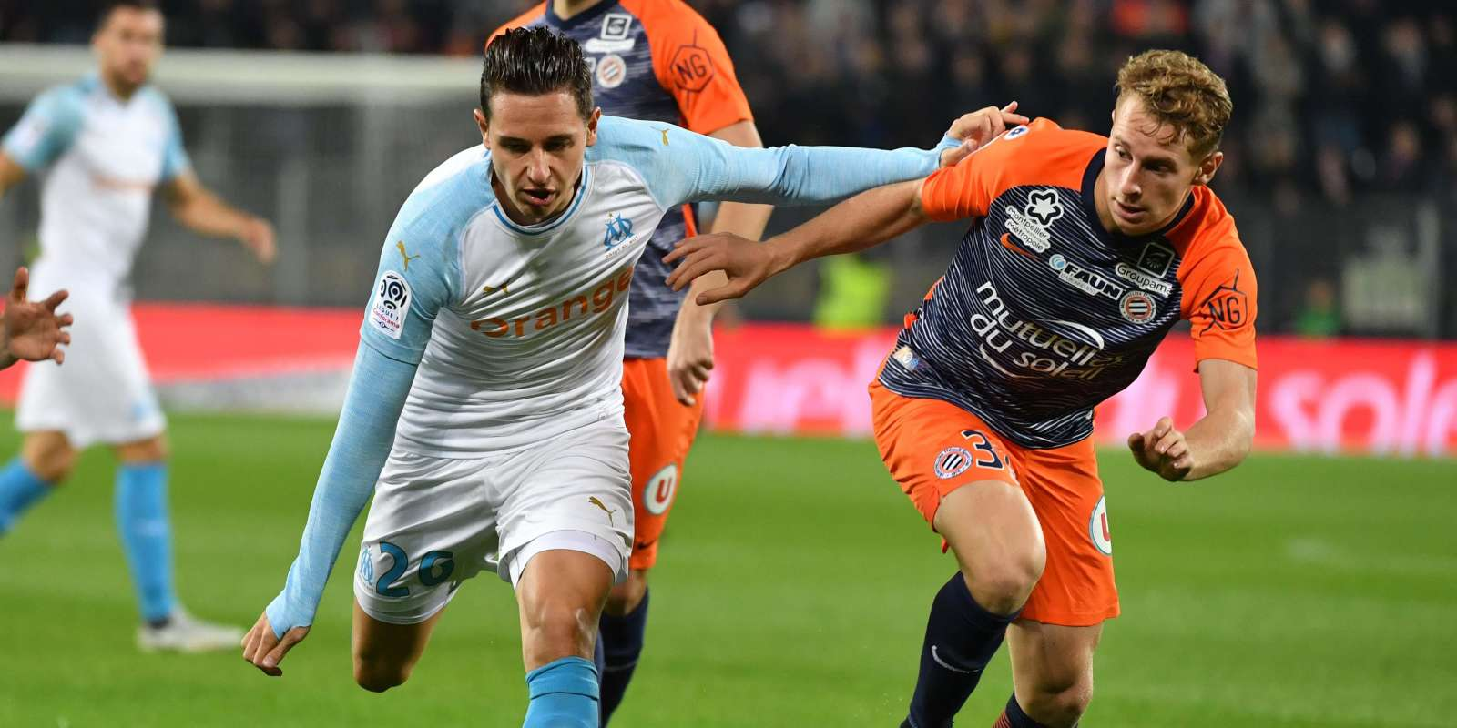 Olympique de Marseille's French midfielder Florian Thauvin (L) vies with Montpellier's French defender Nicolas Cozza (R) during the French L1 football match between Montpellier and Marseille, on November 4, 2018 at the the Mosson stadium in Montpellier, southern France. / AFP / PASCAL GUYOT