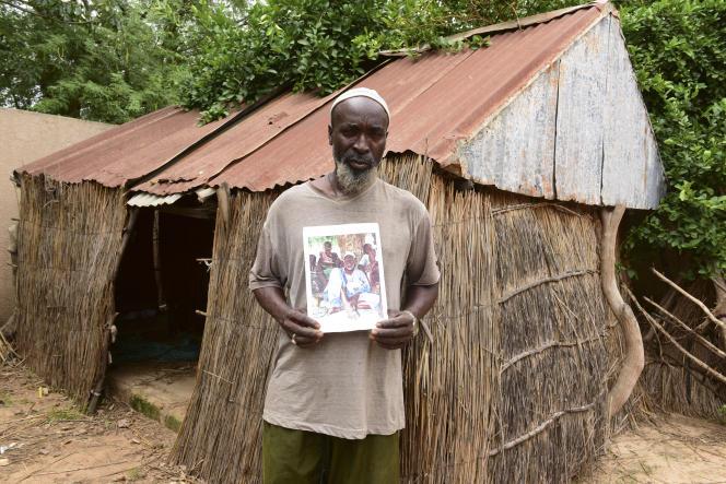 Dans le village de Thiowor, au Sénégal, Babacar Ndiaye pose avec un portrait de son grand-père, Abdulaye Ndiaye, un tirailleur qui combattit pour la France pendant la première guerre mondiale, le 31août 2018.