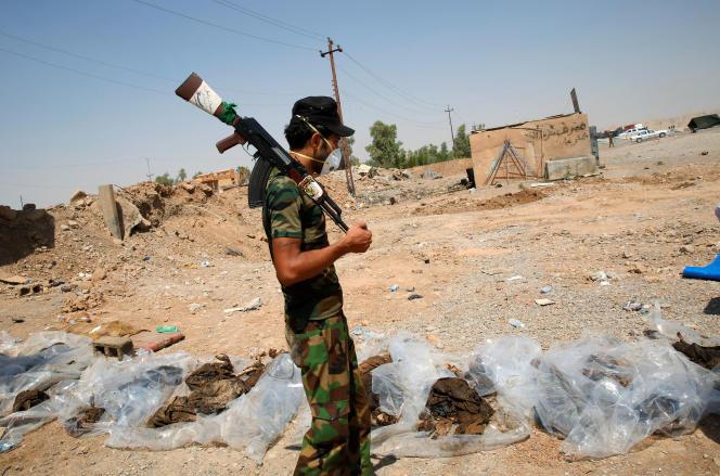 Un combattant chiite examine des corps récemment déterrés d'une fosse près de Sulaiman Pek, le 5 septembre 2014.