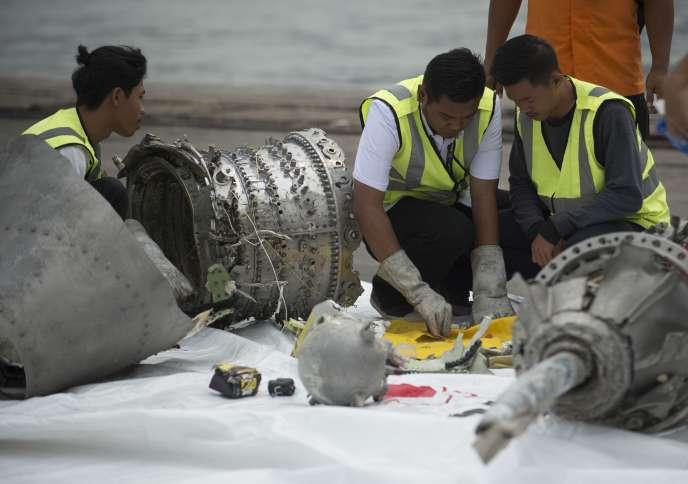 Des enquêteurs examinent un morceau de l'avion de Lion Air, le 7 novembre 2018, à Djakarta.