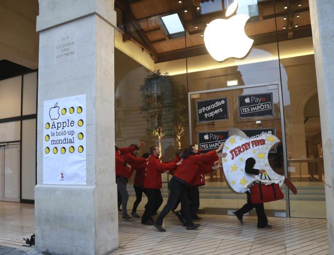 Des membres de l'Association internationale pour la taxation des transactions financières et de l'aide aux citoyens (ATTAC), prennent part à une manifestation devant un magasin Apple à Paris le 10 novembre 2017.