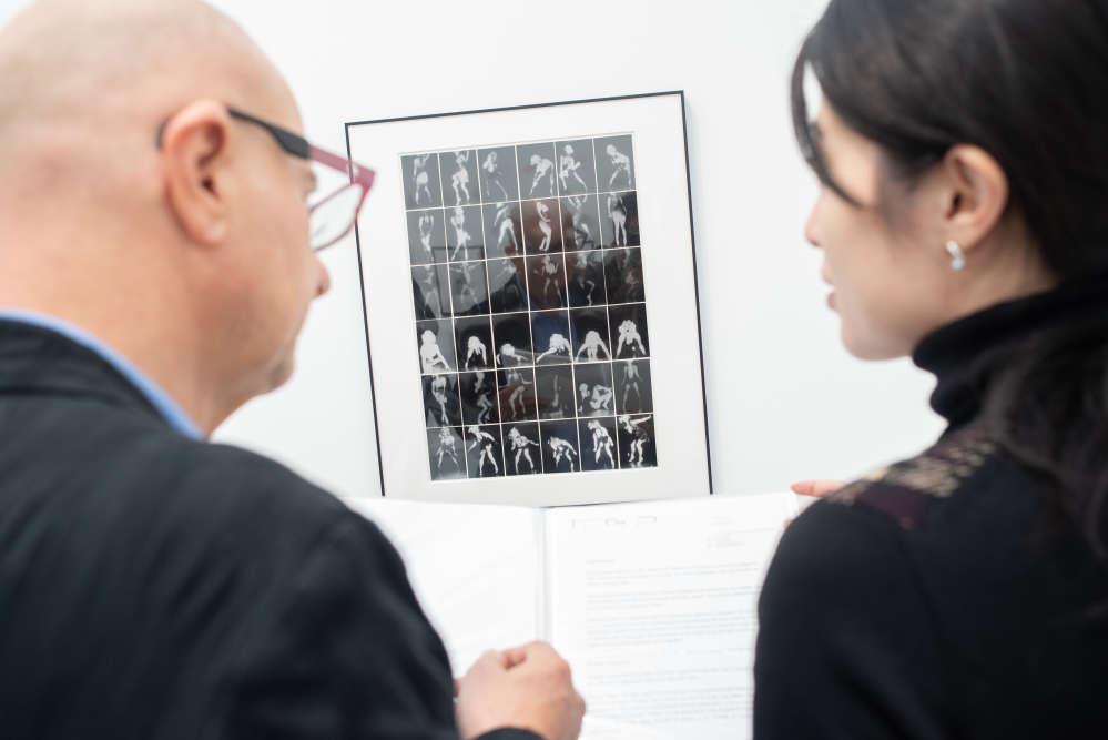 Le collectionneur Artur Walther devant une photo de Tokyo Rumando dans l'espace de la galerie Taka Ishii à Paris Photo 2018, le 7 novembre.