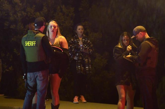 Un policier interroge un témoin de la fusillade qui a fait douze victimes, dans un bar de Thousand Oaks, le soir du 7 novembre.