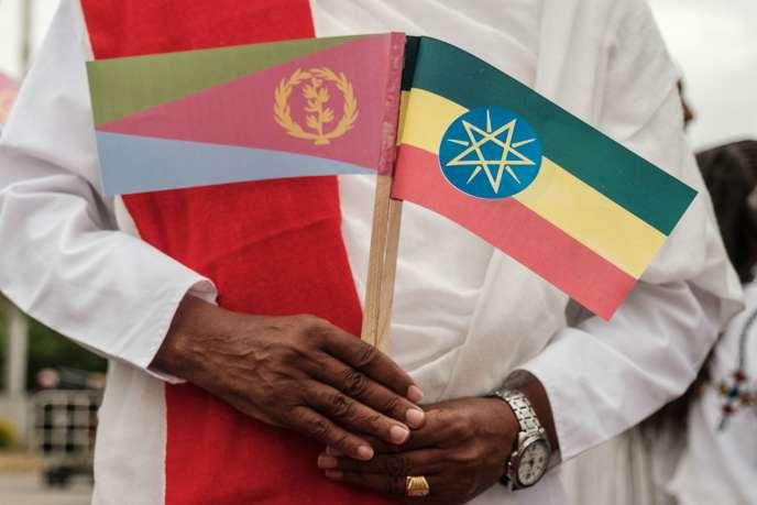 Un homme porte les drapeaux de l'Erythrée (à gauche) et celui de l'Ethiopie lors de l'arrivée du président érythréen à l'aéroport de Godar, en Ethiopie, le 9 novembre 2018.