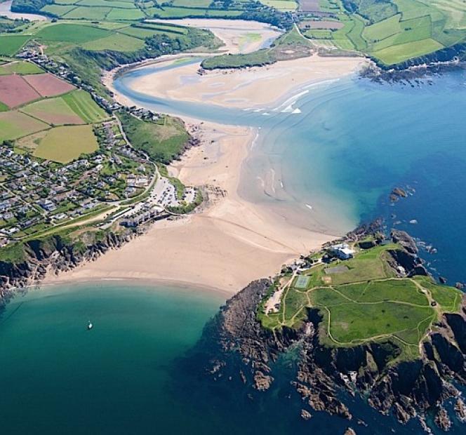 A marée basse, le sable blond de la plage se découvre pour relier Burgh Island à la petite ville de Bigbury-on-Sea (Royaume-Uni).