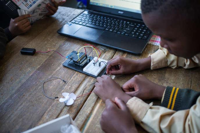 Des élèves assemblent des composants informatiques lors d'un concours de codage et de robotique dans le township d'Ivory Park, en Afrique du Sud, le 12septembre 2018.
