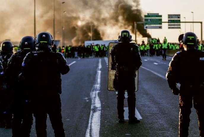 Des gendarmes font face à un blocage de « gilets jaunes» près de Caen, dimanche 18 novembre.