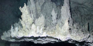 This flange has fluids both trapped underneath and flowing through the top of it to form the smaller chimneys on the top. It is about 1 m across.Image courtesy of University of Washington.Related LinksThe Lost City 2005The Lost City 2005: Chimney FormationNOAA Ocean Explorer .