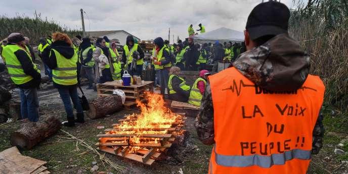 Des manifestants se tiennent près d'un feu en bloquant une route lors d'une manifestation de «Gilets jaunes» pour protester contre les prix élevés du carburant le 19 novembre près du dépôt pétrolier de Frontignan, dans le sud du pays.