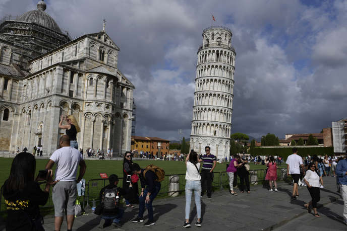 This photograph taken on September 12, 2017, shows tourists posing for photographs at the Pisa tower at the square of Miracles in Pisa. (Photo by MIGUEL MEDINA / AFP)
