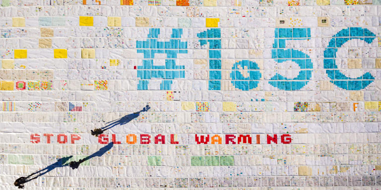 A giant postcard of approximately 2500 square meters made of contributions from over 125'000 individual postcards containing messages aiming to fight climate change and global warming, is pictured on the Aletsch glacier near the Jungfraujoch saddle by the Jungfrau peak, in Switzerland, Friday, November 16, 2018. Each individual postcard includes climate change promises and messages from children and youth originating from 35 countries over the world and aims to establish the Guinness world record of the largest composed postcard with the most overall contributors. The 1.5 degrees Celcius written in the center of the postcard refers to a target of limiting global warming to 1.5°C. (Valentin Flauraud/Keystone via AP)