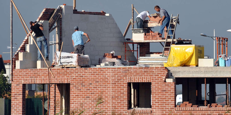 photographie prise le 29 septembre 2011 à Estaires dans le nord, d'ouvriers travaillant sur une maison en cours de construction. L'Union des Maisons Françaises (UMF), le syndicat des constructeurs, a annoncé que les ventes de maisons en secteur diffus devraient baisser en 2011 de 5 à 7% par rapport à 2010. Les tensions sur les prix, en raison des nouvelles obligations des bâtiments basse consommation (BBC) et de la hausse du prix du foncier, expliquent cette diminution des ventes selon l'UMF. AFP PHOTO PHILIPPE HUGUEN (Photo by PHILIPPE HUGUEN / AFP)