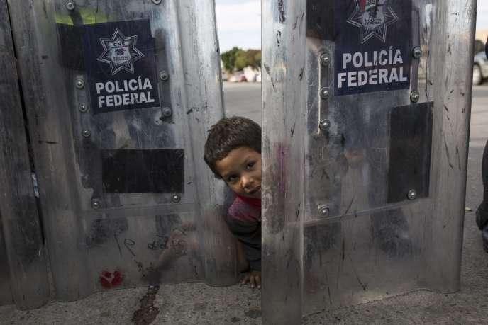 Elias Lopez, un petit Hondurien de trois ans, joue avec les boucliers de la police mexicaine, le 22 novembre à Tijuana, au Mexique.