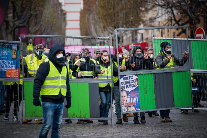 A l'arrière du cortège sur les Champs-Elysées, des jeunes gens en gilets jaunes, équipés pour résister aux lacrymogènes, se sont emparés de barrières de chantier, le 24 novembre.