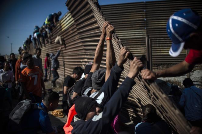 Un groupe de migrants tente de franchir labarrière métallique de délimitation entre le Mexique et les Etats-Unis, à Tijuana, le 25 novembre.