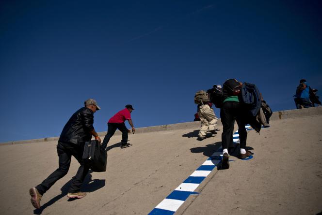 Un groupe de migrants tente de franchir le canal qui mène vers la clôture délimitant la frontière entre le Mexique et les Etats Unis, à Tijuana, le 25 novembre.