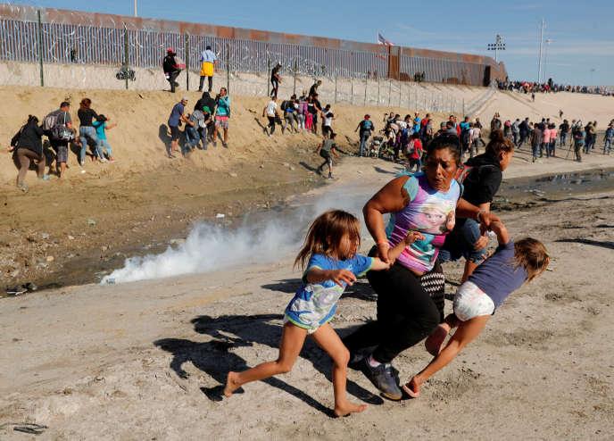 Des migrants fuient les gaz envoyés pour les empêcher de franchir la frontière américaine, à Tijuana (Mexique), le 25 novembre.