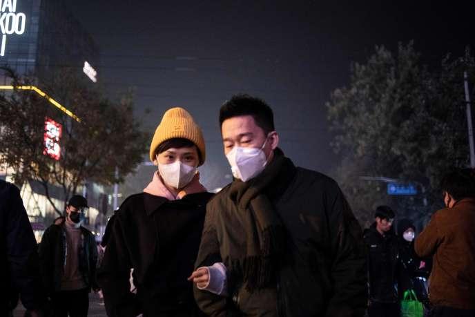 Un couple se protège contre la pollution de l'air à Pékin, fin novembre.