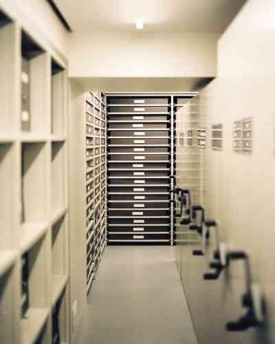 La salle des documents où sont conservés des vêtements stockés à plat ou suspendus dans des housses et des milliers d'archives papier.