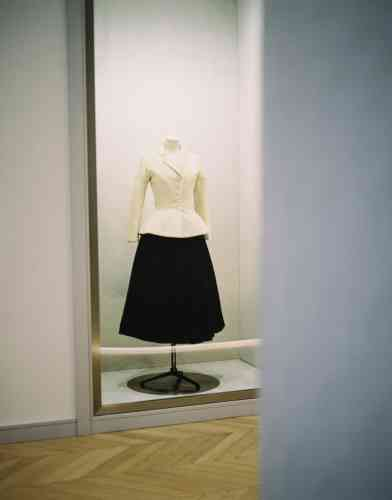 Reproduction du célèbre tailleur Bar. Les modèles nichés dans les trois vitrines jalonnant le couloir entre la bibliothèque et la salle des accessoires de Dior Héritage sont tous des copies, les originaux ne pouvant pas supporter une si longue exposition à la lumière.
