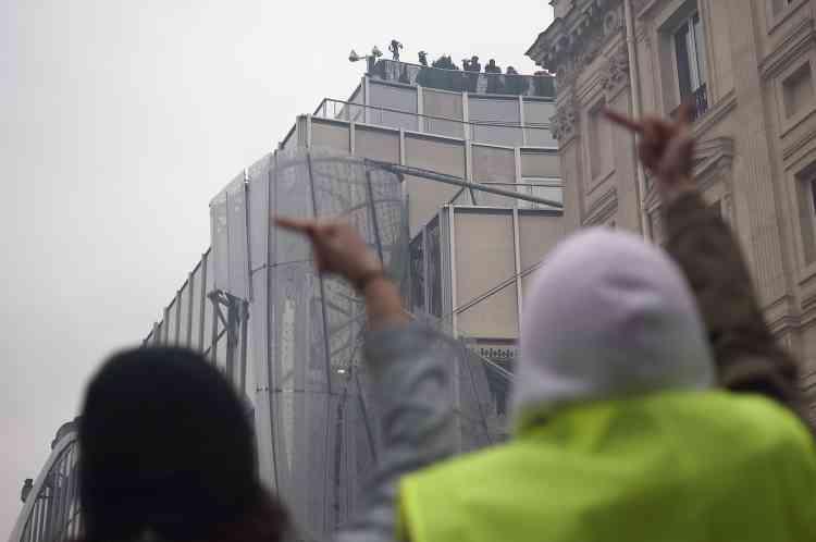 Des journalistes filment le rassemblement des« gilets jaunes» sur les Champs-Elysées à Paris depuis le toit d'un immeuble.