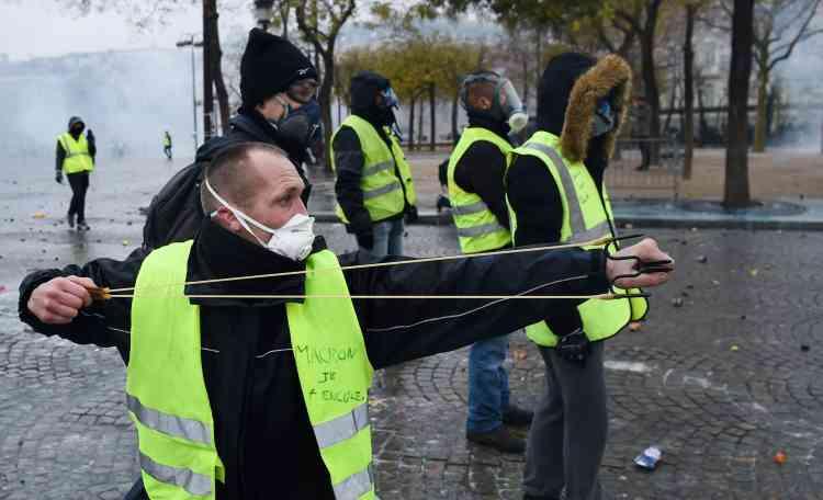 Un « gilet jaune» utilise un lance-pierres sur les Champs-Elysées, à Paris.