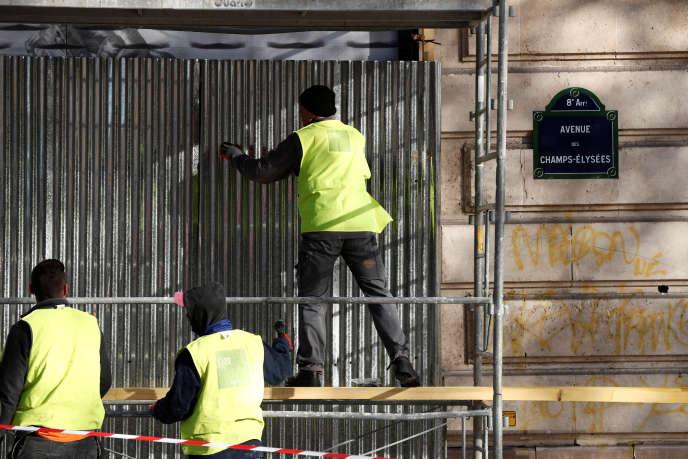 Des vitrines sont protégées à la veille du rassemblement des« gilets jaunes», sur les Champs-Elysées, le 30 novembre.