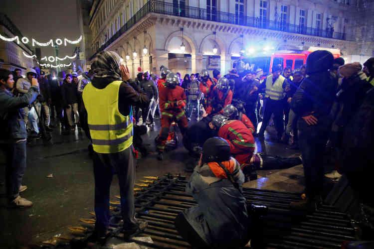 A Paris, des pompiers interviennent pour soigner un « gilet jaune» blessé par la chute d'une grille du jardin des Tuileries que les manifestants ont descellée.