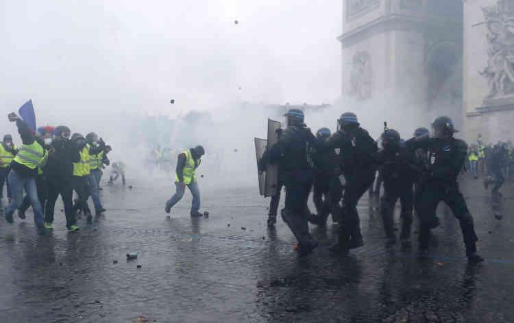 A Paris, sur la place de l'Etoile, la police affronte des groupes violents de « gilets jaunes» sous une pluie de projectiles divers et dans la brume des gaz lacrymogènes.