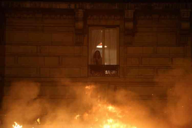 A Paris, une habitante regarde brûler des voitures par sa fenêtre.