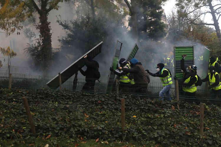 Des « gilets jaunes» utilisent des barrières de chantier comme boucliers contre les canons à eau des forces de l'ordre, dans le quartier des Champs-Elysées.
