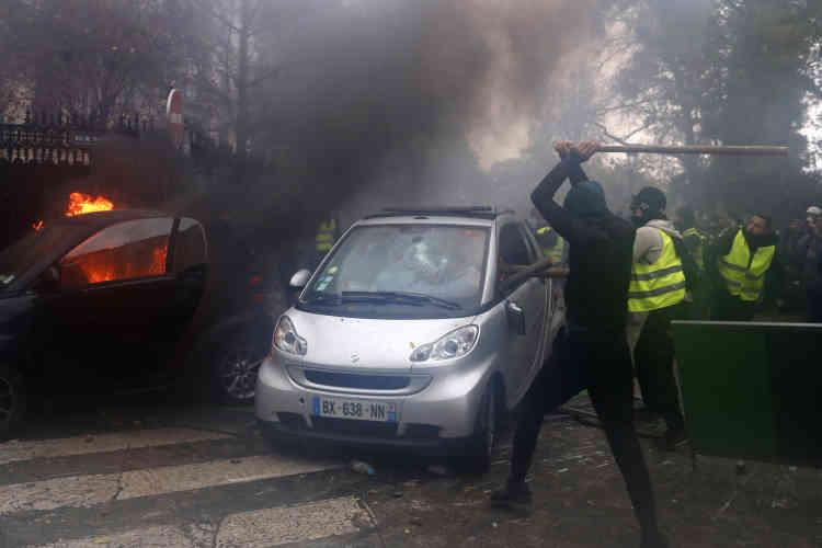 Des « gilets jaunes» détruisent et incendient des véhicules dans le quartier des Champs-Elysées.