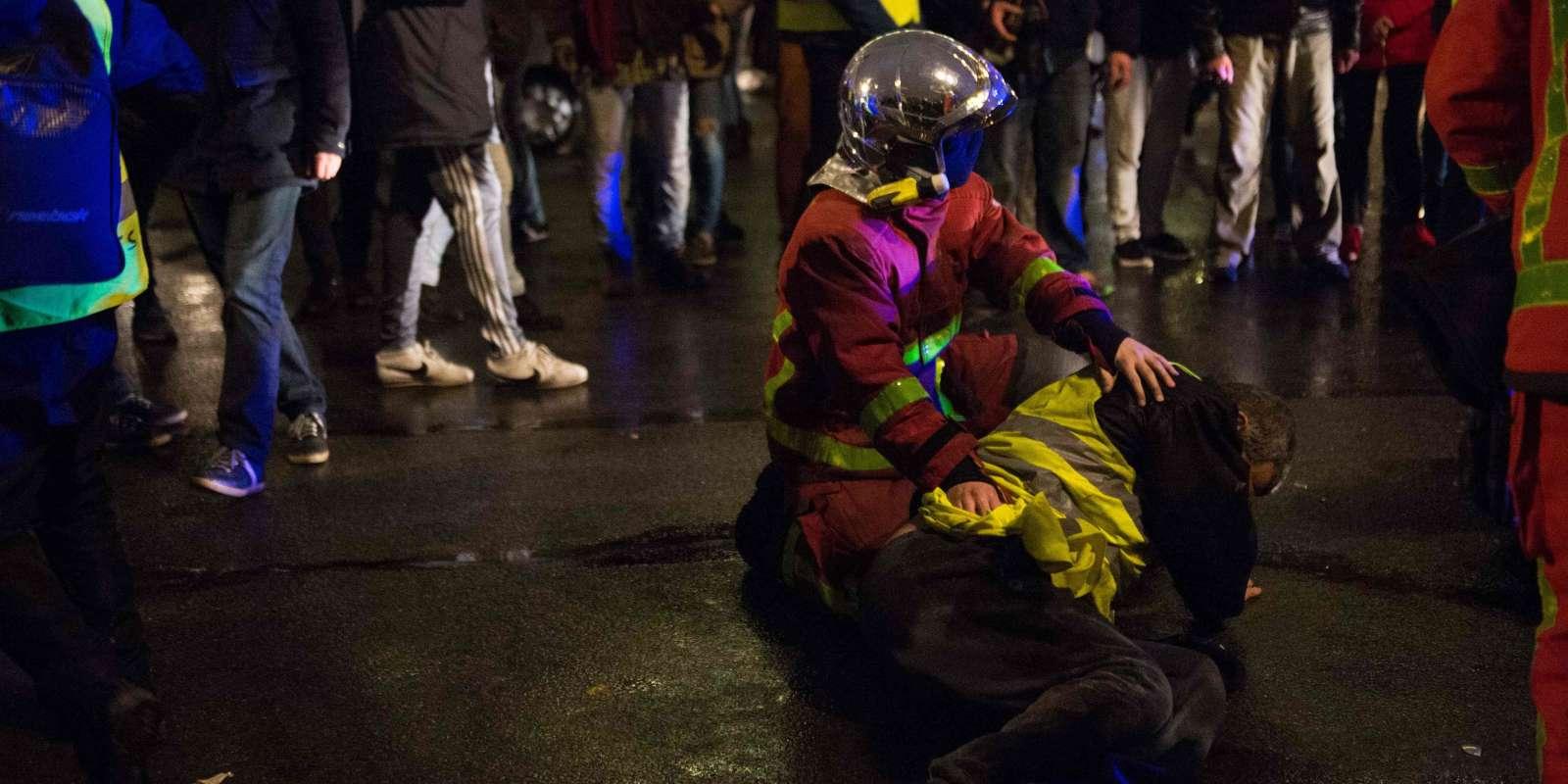 Un sapeur-pompier porte secours à un blessé, près des jardins des Tuileries, à Paris, samedi 1er décembre.