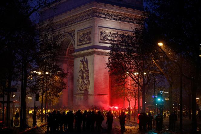 La nuit et la tension tombées, des dizaines de manifestants occupent encore la place de l'Etoile, à Paris, le 1er décembre.