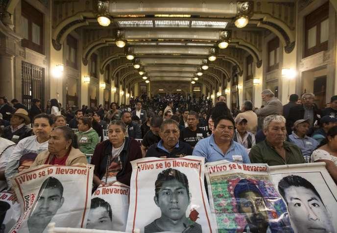 Les proches des 43disparus d'Ayotzinapa brandissant les photos de ces derniers, à Mexico City, le 3décembre.
