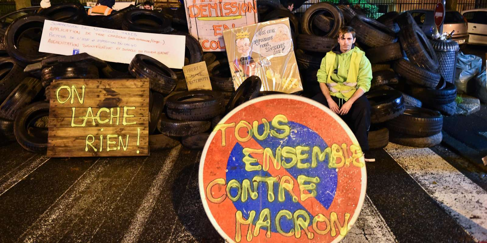 A demonstrator wearing a yellow vest (gilet jaune) sits on a barricade of tires, at the entrance of the Tax Office in Rennes, northwestern France, on December 2, 2018. Thousands took part in a third weekend of