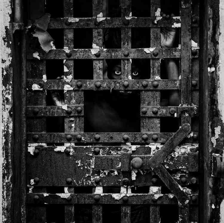 """«Nous avons souhaité inviter Zanele Muholi dans cette exposition pour son travail incessant et engagé d'activiste visuelle sur les questions du droit à la liberté, à la vie, dans son pays (Afrique du Sud). La photo est extraite de sa série d'autoportraits""""Somnyama Ngonyama"""". » Elle a été réalisée dans une prison historique des Etats-Unis, décrit comme le premier centre pénitentiaire du monde. Le regard fixe et volontaire évoque la résilience face aux différentes formes d'incarcération subies quotidiennement par les personnes de couleur et autres communautés marginalisées dans le monde.»"""