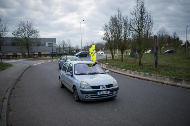 Un automobiliste manifeste son soutien en passant le barrage filtrant des « gilets jaunes» du rond-point de Cocherel, à Evreux, le 5 décembre.