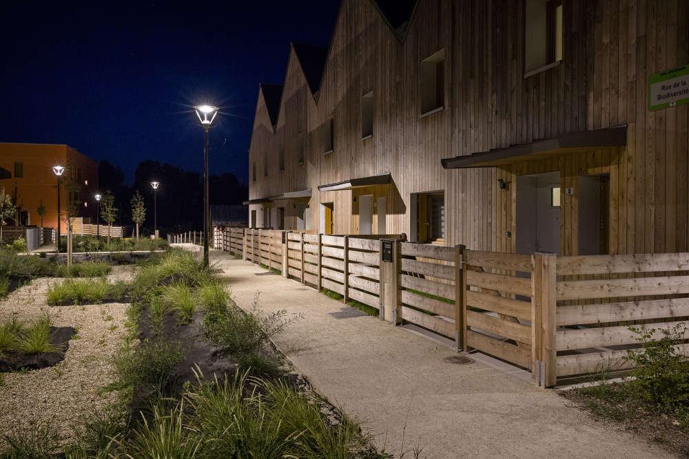 Le long des allées, des seuils en bois ou végétalisés ménagent le voisinage. De nuit, la lumière est dirigée vers le sol pour réduire le halo.