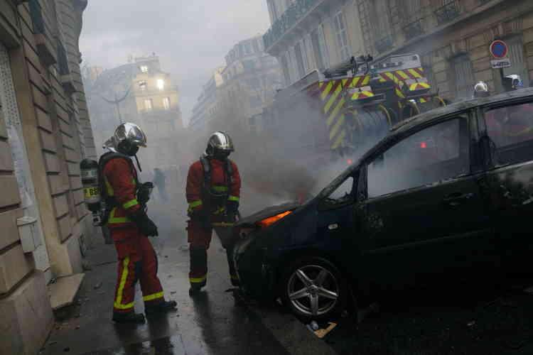 A Paris, rue Newton, au croisement de l'avenue Marceau, non loin des Champs-Elysées, des pompiers interviennent sur des véhicules en feu.