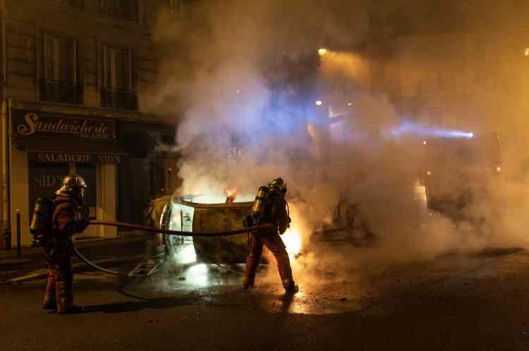 Des pompiers interviennent sur des feux de voitures dans le 17e arrondissement de Paris.
