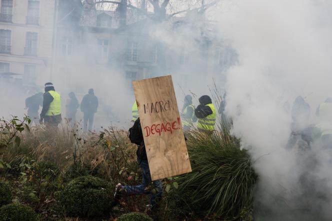 Un « gilet jaune» court dans un buisson son panneau anti-Macron au milieu des gaz lacrymogènes, à Nantes, le 8 décembre.